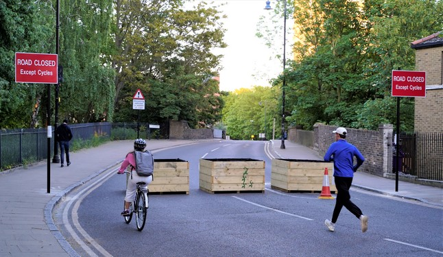 Three wooden planters placed across the carrigeway to block motor vehicles but allow walkers and cyclists free passage